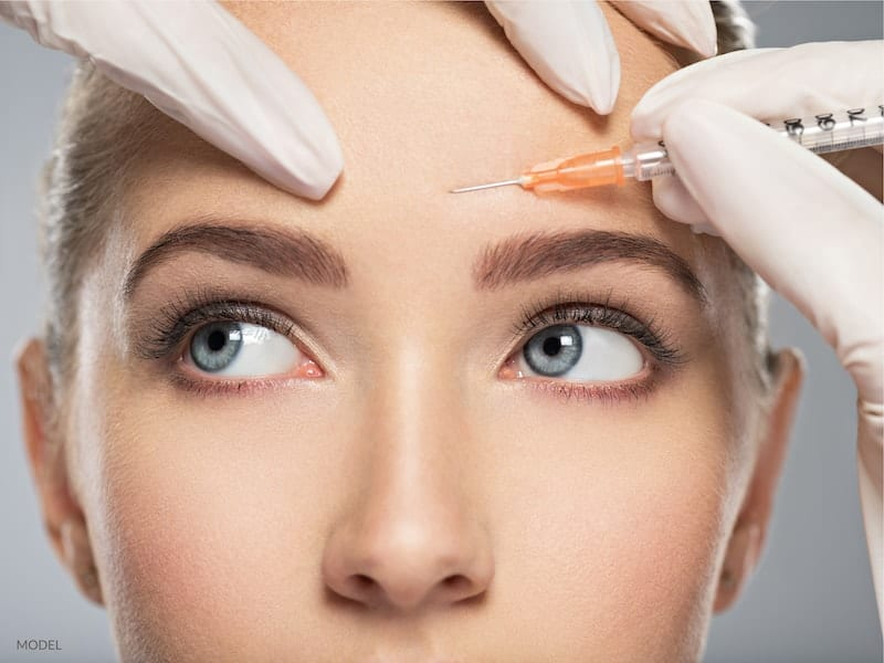 Woman getting a BOTOX® Cosmetic injection in her forehead.